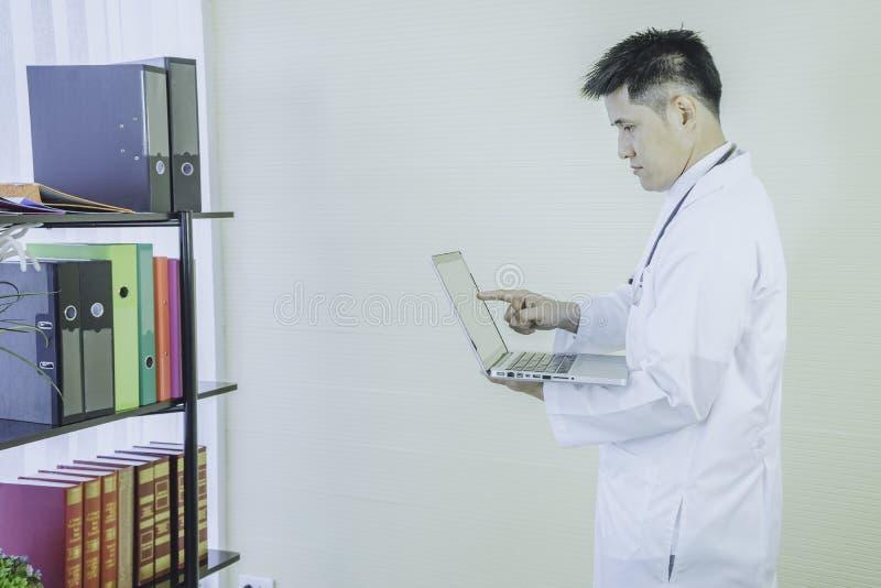 Il computer portatile diritto della tenuta di giovane medico asiatico per trovare le informazioni del lavoro, ha stetoscopio che  fotografie stock libere da diritti