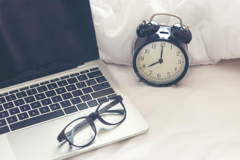 Il computer portatile e la sveglia di mattina su un letto bianco Copi lo spazio fotografie stock