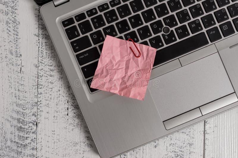 Il computer portatile metallico d'avanguardia ha schiacciato il fondo d'annata rustico di legno di menzogne di carta colorato del fotografia stock libera da diritti