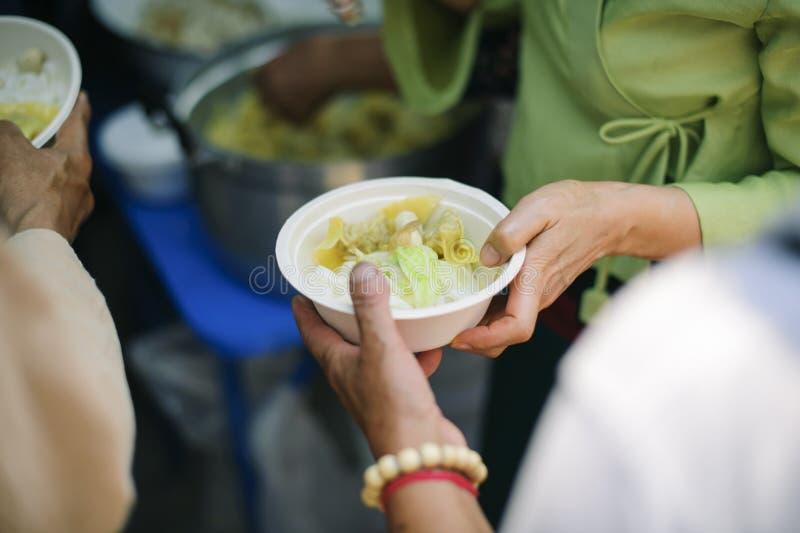 Il concetto dei problemi di vita, fame nella società: concetto dell'alimento di carità per il povero: Nutrendo a mano al bisognos immagini stock