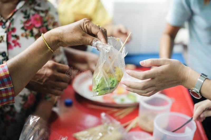 Il concetto dei problemi di vita, fame nella società: concetto dell'alimento di carità per il povero: Nutrendo a mano al bisognos fotografie stock