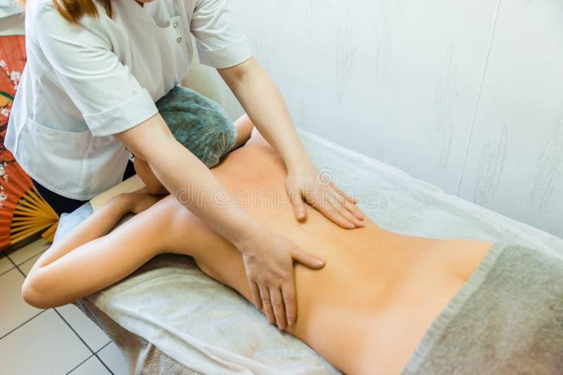 Il concetto del trattamento posteriore di massaggio Massaggiatore femminile che fa massaggio alla ragazza fotografie stock libere da diritti