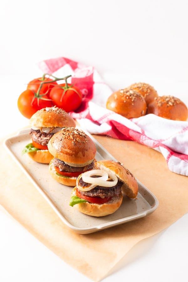 Il concetto dell'alimento casalingo rinforza gli hamburger per servire sul piatto quadrato su fondo bianco con lo spazio della co immagine stock