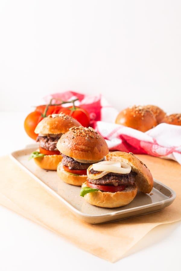 Il concetto dell'alimento casalingo rinforza gli hamburger per servire sul piatto quadrato su fondo bianco con lo spazio della co immagine stock libera da diritti