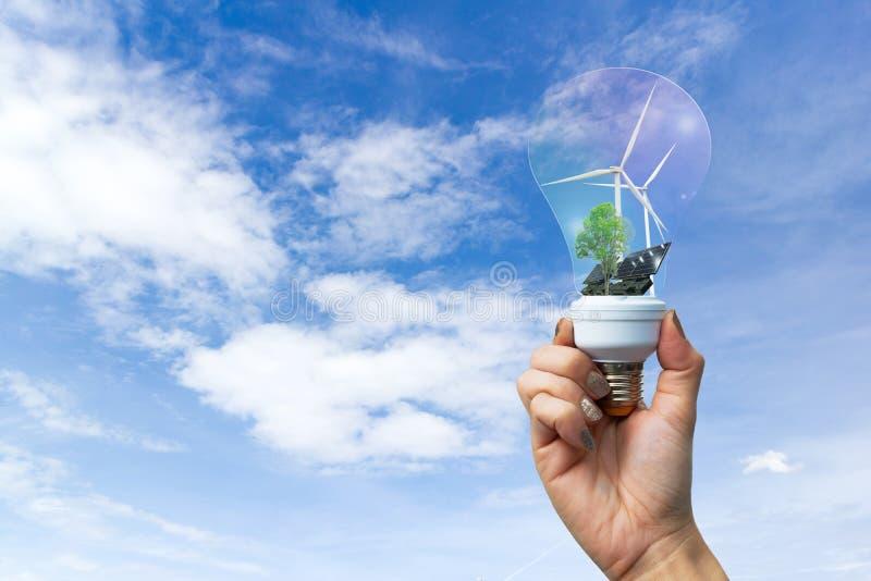 Il concetto dell'ecologia ricicla la mano che sviluppa il generatore eolico pulito di energia elettrica e la pila solare il futur fotografia stock