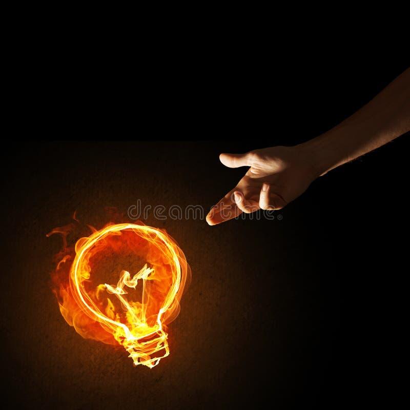 Il concetto dell'elettricità o l'ispirazione con la bruciatura la lampadina e della creazione gesture immagine stock