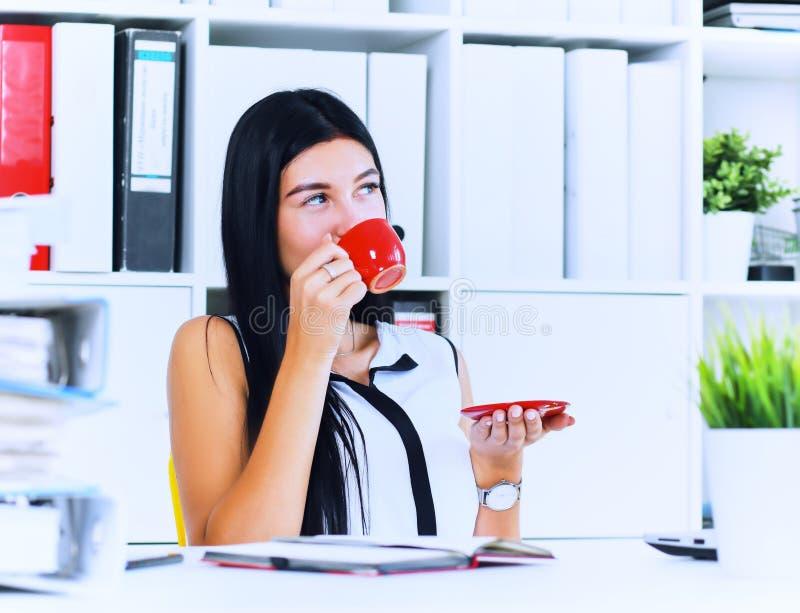 Il concetto della pausa caffè, donna di affari beve il caffè preparato istante mentre lavora con una pila di carte che si siedono fotografia stock libera da diritti