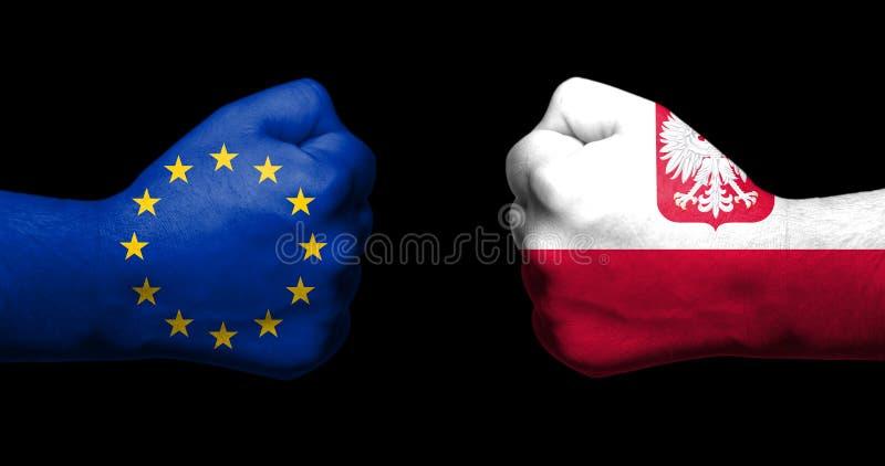 Il concetto delle relazioni/conflitto fra la Polonia e l'Unione Europea ha simbolizzato da due pugni chiusi opposti a immagine stock