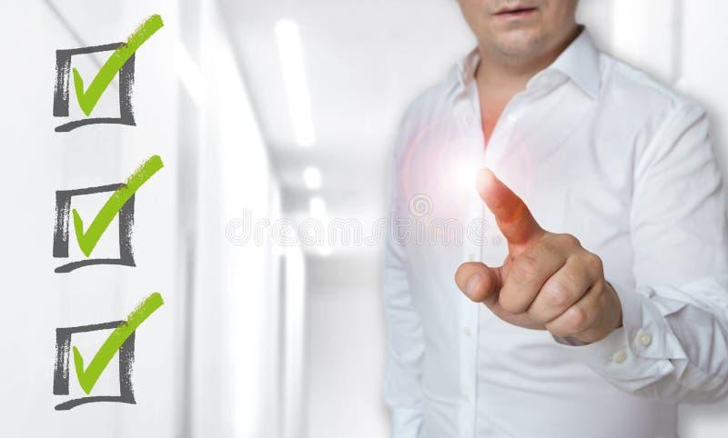 Il concetto dello schermo attivabile al tatto della lista di controllo è azionato dall'uomo fotografie stock