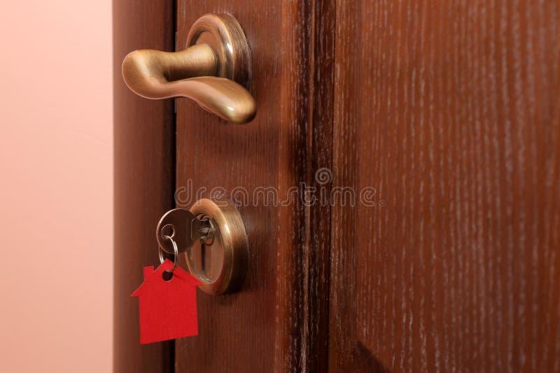 Il concetto di acquisto della casa Chiavi con la casa del keychain nel primo piano della serratura di porta fotografie stock libere da diritti