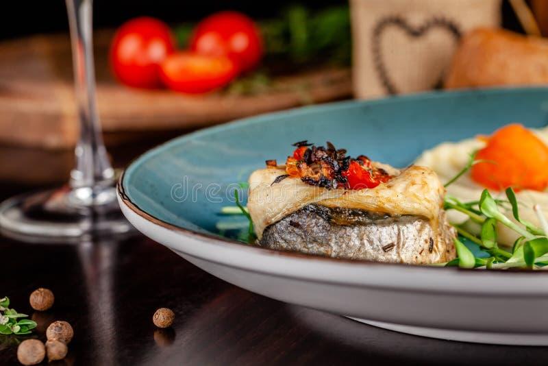 Il concetto di cucina italiana Pesce al forno della spigola con le verdure e le purè di patate Un vetro di vino bianco sulla tavo immagini stock
