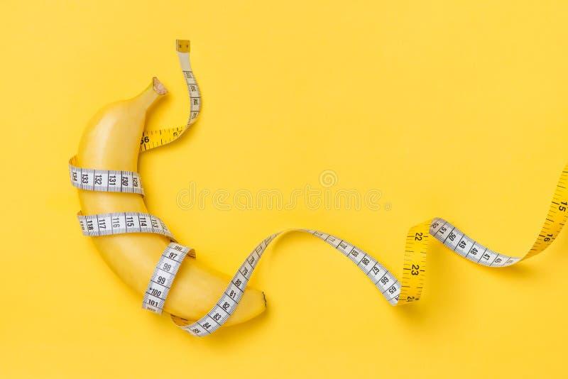 Il concetto di dieta, di forma fisica e di salute ha presentato dall'involucro giallo della banana fotografie stock libere da diritti