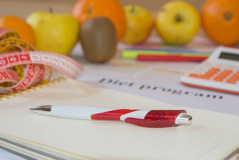 Il concetto di essere a dieta, peso in eccesso perdente Frutti, Bilancia, calcolatore e centimetro su una tavola di legno fotografie stock libere da diritti