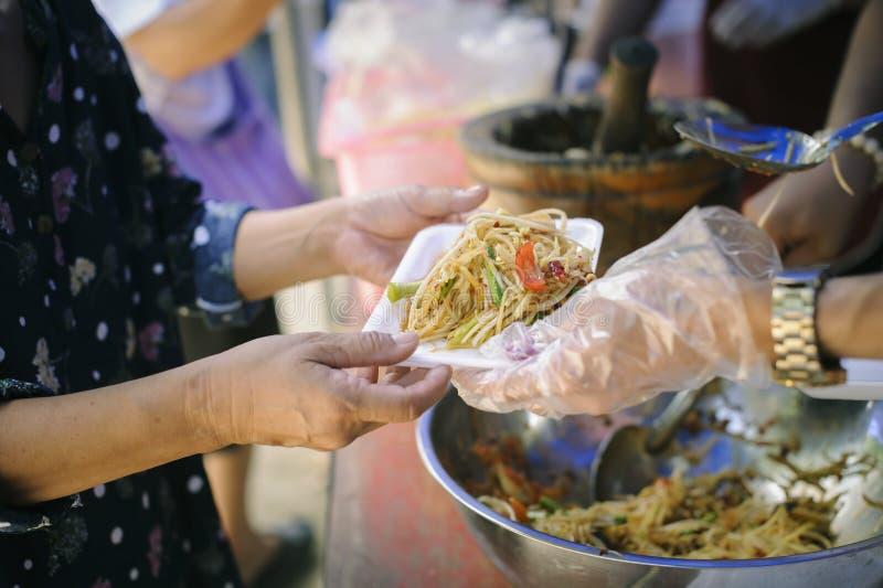 Il concetto di fame: Bisogni dell'alimento del povero nell'aiuto della società con donazione dell'alimento: Il barbone prende l'a fotografie stock libere da diritti
