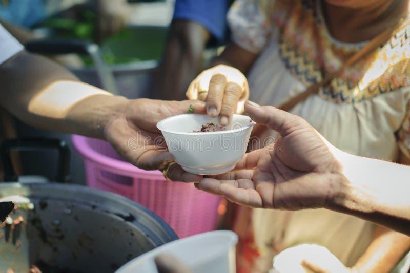 Il concetto di fame: Bisogni dell'alimento del povero nell'aiuto della società con donazione dell'alimento: Il barbone prende l'a fotografia stock