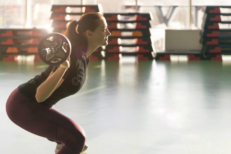 Il concetto di fedeltà, sport, sollevamento di forze e di persone - donna sportiva che si esercita con barbell in palestra immagine stock libera da diritti