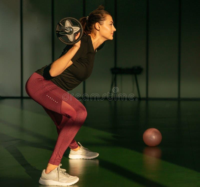 Il concetto di fedeltà, sport, sollevamento di forze e di persone - donna sportiva che si esercita con barbell in palestra fotografia stock