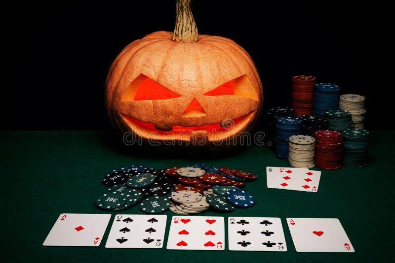 Il concetto di Halloween La zucca spaventosa diabolica gioca il poker Jack L fotografia stock libera da diritti