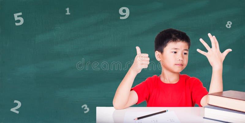 Il concetto di istruzione, i ragazzi si siede nel compito di per la matematica immagine stock libera da diritti