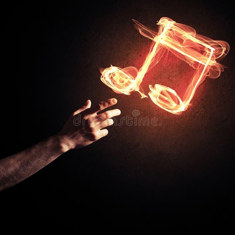 Il concetto di musica ha presentato dall'icona bruciante del fuoco e dal gestur della creazione fotografie stock libere da diritti