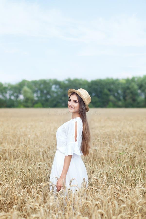 Il concetto di pace dello spirito Una giovane donna attraente cammina in un giacimento di grano dorato La ragazza sta guardando i fotografia stock
