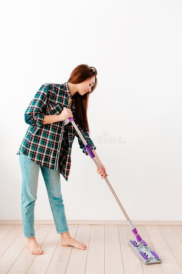 Il concetto di pulizia Giovane donna caucasica che lava pavimenti C'è un muro bianco sullo sfondo Verticale Copia spazio immagine stock