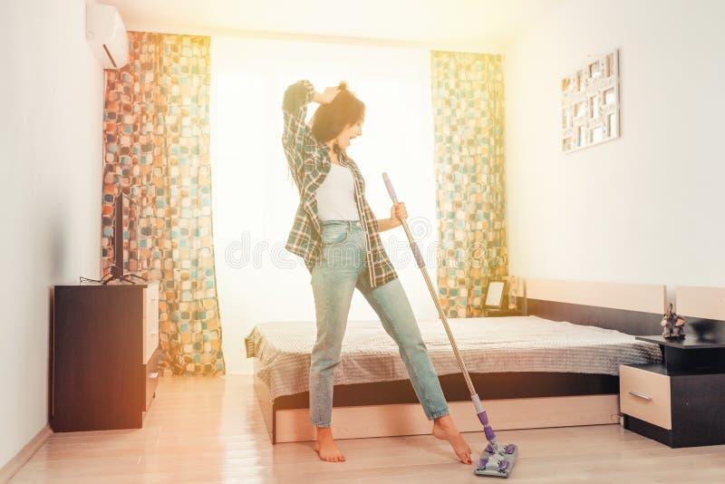Il concetto di pulizia Una giovane e slanciata brunetta pulisce la casa e canta canzoni in uno straccio, come in un microfono Luc fotografia stock