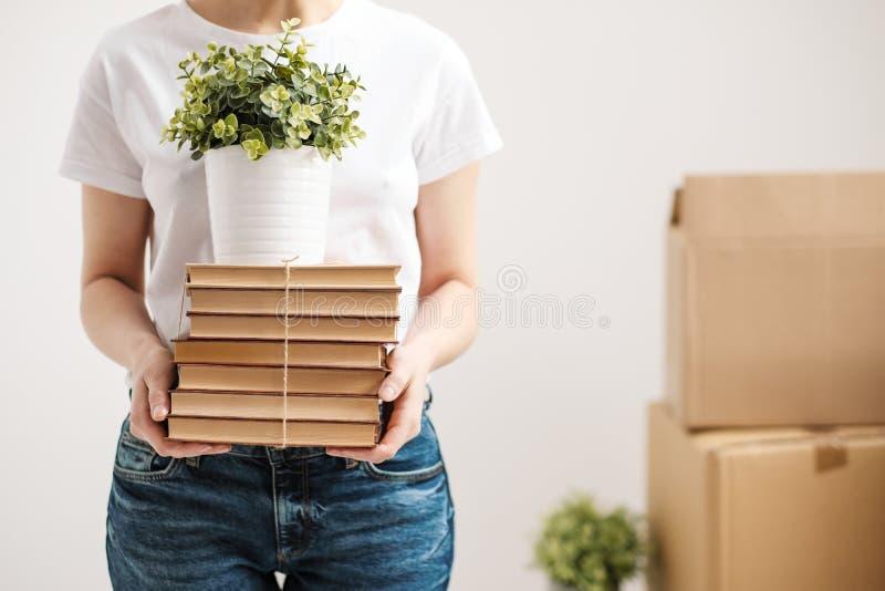 Il concetto di rilocazione e di muoversi verso una nuova casa Il primo piano, mani femminili tiene un mucchio dei libri e di una  fotografia stock libera da diritti