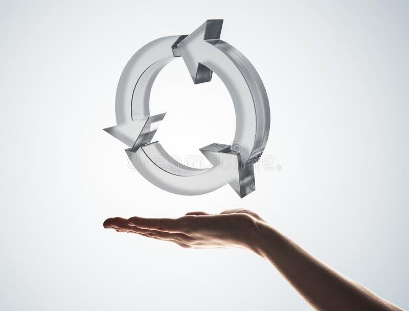 Il concetto di riutilizzazione e ricicla presentato dall'icona di vetro in palma immagine stock