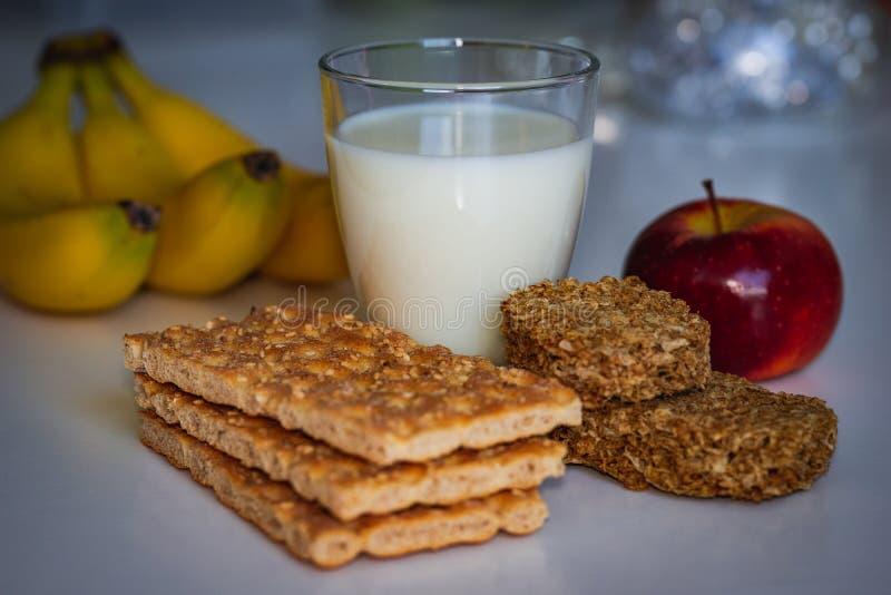 Il concetto di salute, dieta, nutrizione adeguata Cracker del grano, pani croccanti, cracker del grano, latte, banane e mela sani fotografia stock