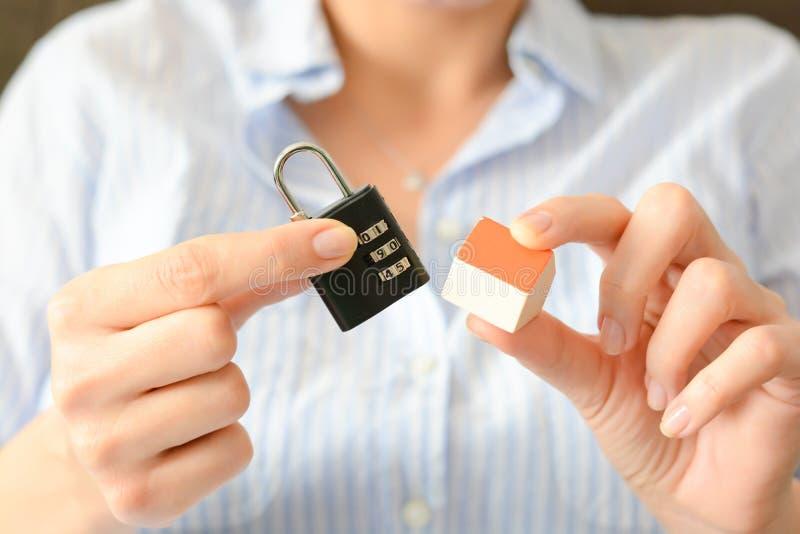 Il concetto di sicurezza domestica o di assicurazione con la serratura di cifra ha tenuto oltre ad una casa miniatura fotografia stock