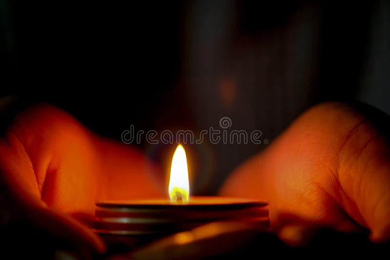 Il concetto di speranza e di preghiera della candela si accende in mani immagini stock libere da diritti
