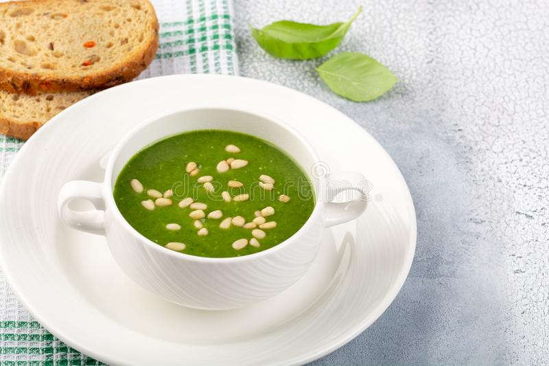 Il concetto di un alimento sano, vegetariano o dietetico: minestra crema degli spinaci, con i pinoli ed il basilico Con le fette  fotografie stock libere da diritti