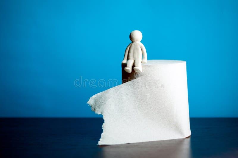 Il concetto di un uomo che si siede su un rotolo della carta igienica fotografia stock