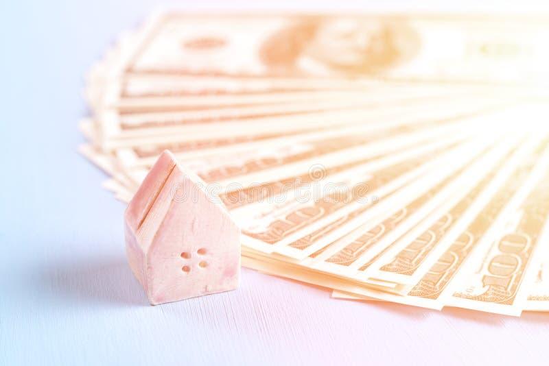Il concetto di una casa del giocattolo su un fondo delle banconote in dollari, luce, luce solare, tonificata immagini stock libere da diritti