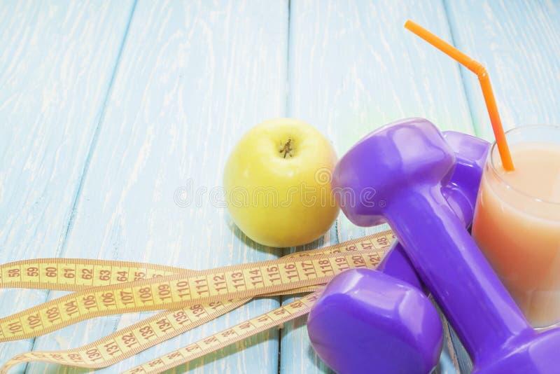 Il concetto di una dieta sana Piccole teste di legno, succo Banane Arance mele Stile di vita sano sport Barra di forma fisica dei immagini stock