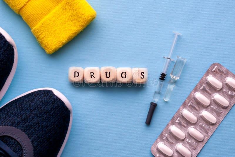 il concetto di verniciatura nello sport L'iscrizione si trascina un fondo blu Scarpe di sport, pillole, siringa con medicina, sup immagine stock libera da diritti