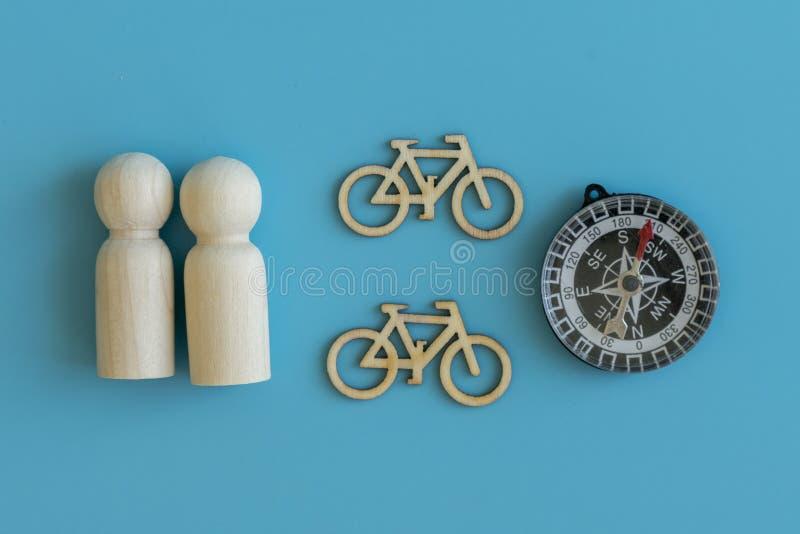 Il concetto di viaggio sulle biciclette, uno stile di vita sano Figure di legno della gente e dei aeolopes su un fondo blu fotografie stock libere da diritti