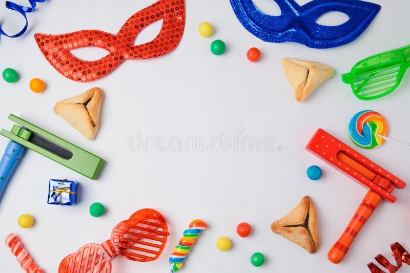 Il concetto ebreo di Purim di festa con hamantaschen i biscotti, la maschera di carnevale ed il noisemaker su fondo bianco fotografia stock libera da diritti