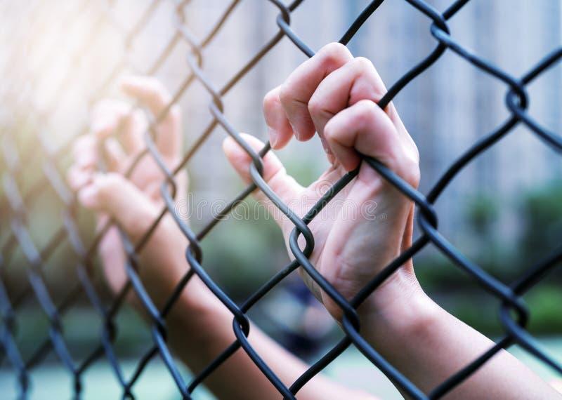 Il concetto internazionale del giorno di diritti umani, donne passa sul recinto del collegamento a catena Depresso, difficoltà e  fotografie stock