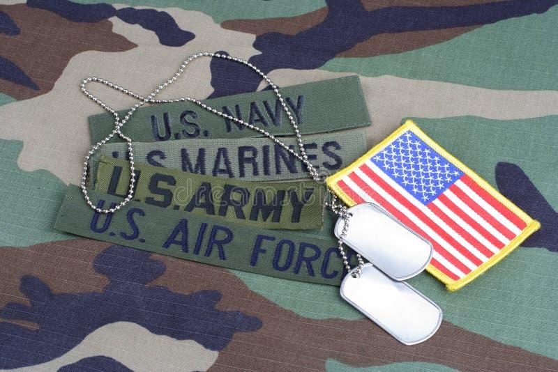 Il concetto militare degli Stati Uniti con nastri adesivi del ramo e le medagliette per cani sul cammuffamento del terreno boscos fotografia stock libera da diritti