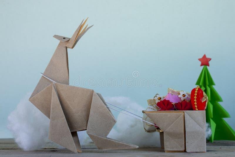 Il concetto piega la carta è una renna che prepara dare i regali ai bambini al giorno di Natale immagine stock libera da diritti