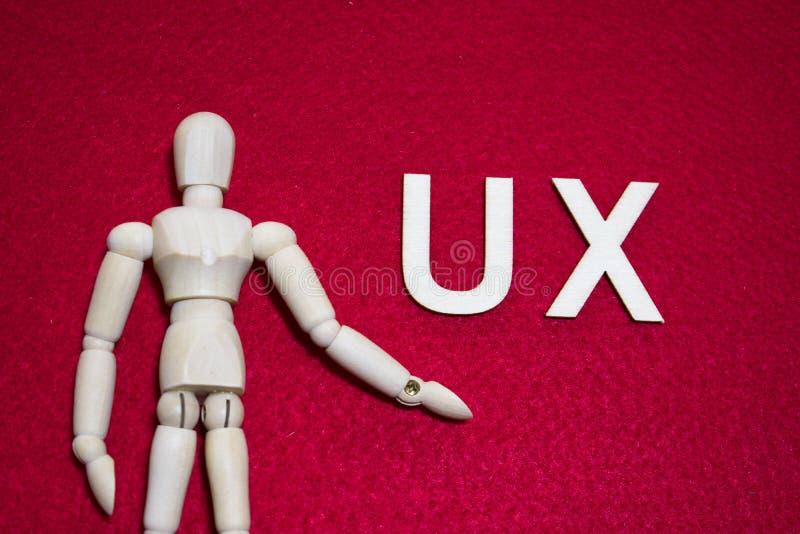 Il concetto UX di esperienza utente, burattino di legno sull'acrilico di colore rosso ha ritenuto il tessuto immagine stock