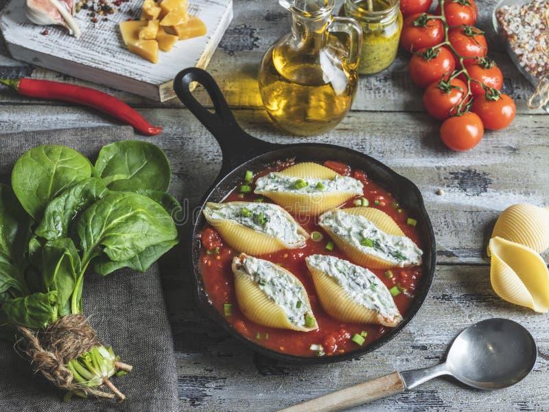 Il conchiglioni cucinato della pasta ha farcito gli spinaci ed il formaggio, salsa al pomodoro immagini stock