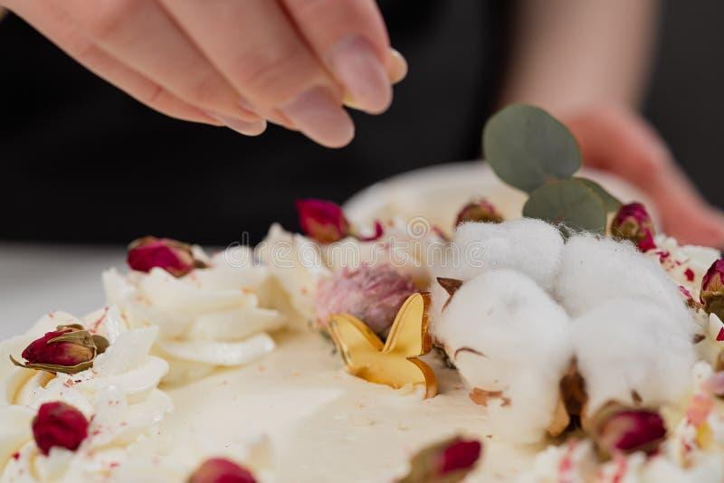 Il condater spruzza il dolce con le mandorle e la noce di cocco grattate Primo piano di una mano e delle briciole di versamento fotografia stock libera da diritti