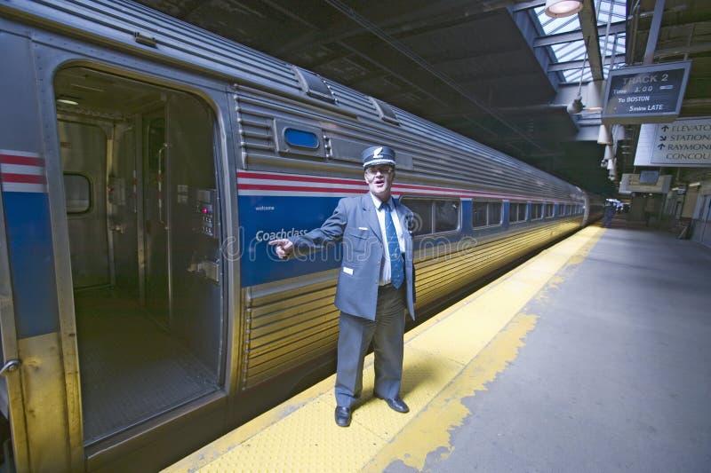 Il conduttore al binario del treno dell'Amtrak annuncia tutti a bordo alla stazione ferroviaria sul modo a New York, New York, Ma fotografia stock libera da diritti