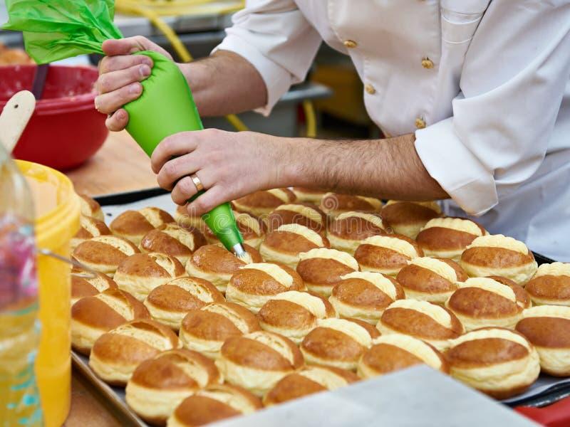 Il confettiere sta preparando il panino con crema immagine stock libera da diritti