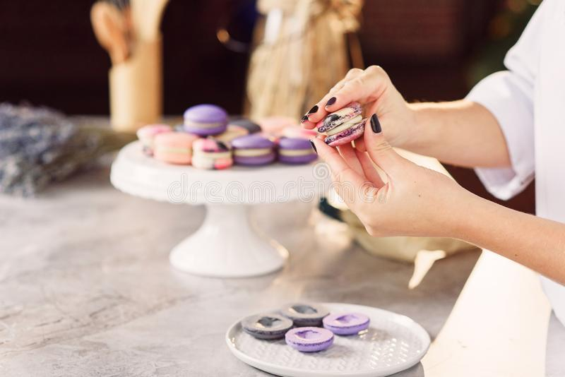 Il confettiere unisce le parti dei macarons a vicenda facendo uso di una crema fotografia stock