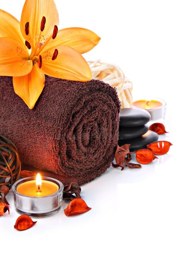 Il confine di massaggio della stazione termale con l'asciugamano ed il giglio arancio fioriscono immagine stock