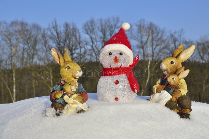 Il coniglietto di pasqua incontra il pupazzo di neve fotografie stock libere da diritti
